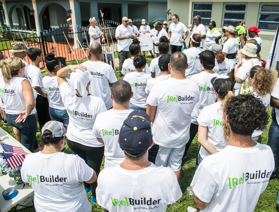 Group of Rebuilding Together volunteers standing together in white shirts, facing away from camera