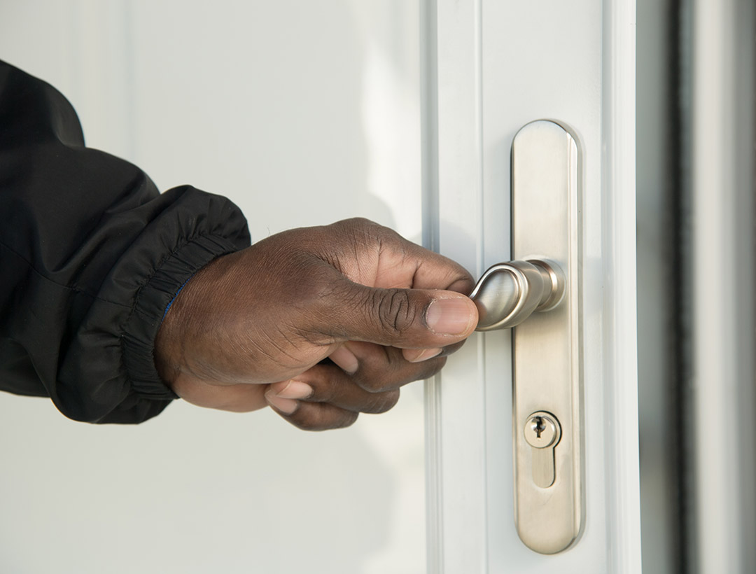 A neighbor's hand opening a door with a lever handle.