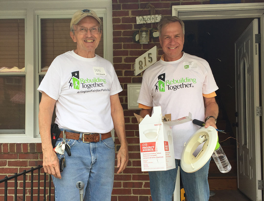 Two volunteers standing on a porch, smiling and holding an empty box of a lighting fixture.