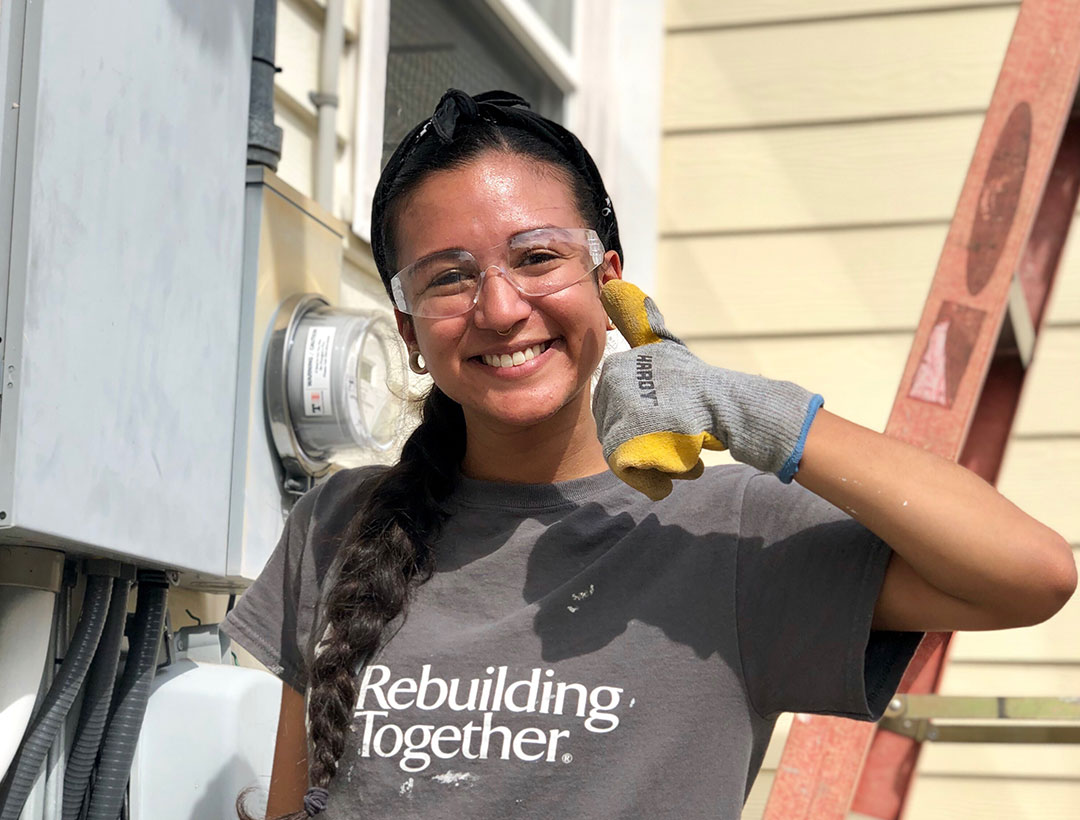 AmeriCorps member giving a thumbs up in work gloves on rebuild project site